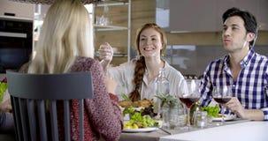 Roodharigevrouw en man die kip en aardappels en het spreken eten Vier gelukkige echte spontane vrienden genieten van hebbend lunc stock video