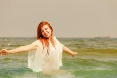 Roodharigevrouw het spelen in water tijdens zomer royalty-vrije stock afbeeldingen