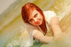 Roodharigevrouw het stellen in water tijdens zomer Royalty-vrije Stock Afbeeldingen
