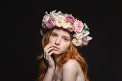 Roodharigevrouw met kroon van bloemen op hoofd stock fotografie