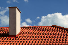 Roof. Red tiles roof and chimney with blue sky Stock Images