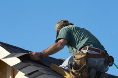 On the roof. Worker on roof putting shingles down stock photo