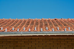 Roof. Gutter, brick wall, sky Royalty Free Stock Photos