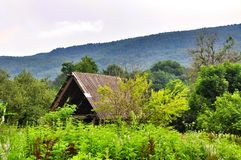 The roof of abandoned house mountains in the background Stock Photo