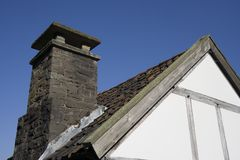 Roof of an ancient house. Against a deep blue sky Stock Photos