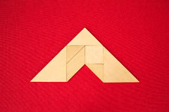 Roof or arrow showing direction. Flat lay - pictogram of roof, geometrical abstract background or arrow showing direction made of wooden tangram pieces. Unicolor stock photo