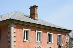 The roof is of asbestos roof slate. Old brick house. Old roof slates and chimney Royalty Free Stock Photography