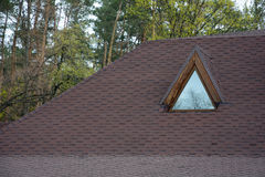 Roof Asphalt Shingles and Attic Mansard Window. Roofing Construction. Roofing Repair. stock photo