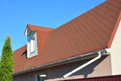 Roof Asphalt Shingles with Moss. Rain Gutter Pipeline with Downspout Pipe and Attic Mansard Window. Stock Photography