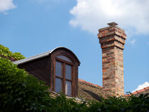 Roof with attic and chimney. And green Ivy against blue sky Royalty Free Stock Photo