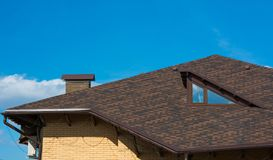 Roof with attic and chimney under clear blue sky. Cottage roof with attic and chimney under clear blue sky Stock Images