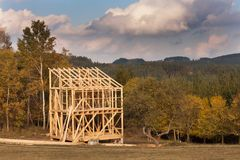 Roof beams. Sunny autumnal evening at the construction site of a wooden house. Unfinished house. Stock Images