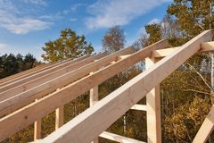 Roof beams. Sunny autumnal evening at the construction site of a wooden house. Unfinished house. Stock Photography