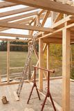 Roof beams. Sunny autumnal evening at the construction site of a wooden house. Unfinished house. Royalty Free Stock Photo