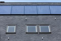 Roof of black slate tiles, roof Windows and fixed solar panels.  Stock Photo
