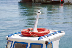 Roof of a boat with orange lifebuoy in  harbor Royalty Free Stock Photos