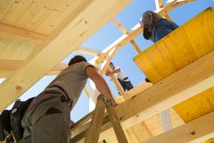 Builders at work with wooden roof construction. Roof builders mounting prefabricated wooden roof construction. Construction industry concept Stock Image