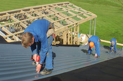 On the roof. Builders working on the roof of a large house Stock Images