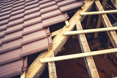 Roof building with ceramic brown tiles on wooden, timber structure. Geometric distribution of roof tiles at house construction Stock Photography