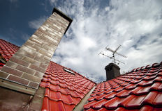 Roof and chimney. Tall chimney on a red tiles roof Stock Photos