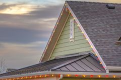 Roof with christmas lights against cloudy sky. Close up view of a roof decorated with Christmas lights against a cloudy sky. Beautiful homes in Daybreak, Utah stock photography