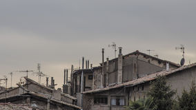 Roof cityscape with many old chimneys on a grey cloudscape Royalty Free Stock Photos