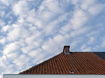 Roof with clouds. Red roof in the sky Royalty Free Stock Images