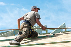 Roof construction. Roofer on a sloping pitched roof fitting wooden planks royalty free stock photo