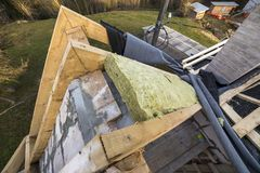 Roof construction and insulation with mineral wool. Wooden beams frame on walls of hollow foam insulation blocks. Roofing. Underlayment, water-resistant stock photos