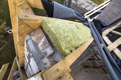 Roof construction and insulation with mineral wool. Wooden beams frame on walls of hollow foam insulation blocks. Roofing. Underlayment, water-resistant royalty free stock photography