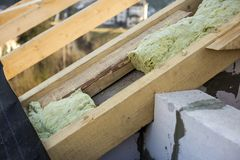 Roof construction and insulation with mineral wool. Wooden beams frame on walls of hollow foam insulation blocks. Roofing. Underlayment, water-resistant royalty free stock photos
