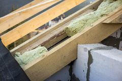 Roof construction and insulation with mineral wool. Wooden beams frame on walls of hollow foam insulation blocks. Roofing. Underlayment, water-resistant royalty free stock images