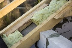 Roof construction and insulation with mineral wool. Wooden beams frame on walls of hollow foam insulation blocks. Roofing. Underlayment, water-resistant stock photo