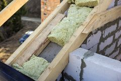 Roof construction and insulation with mineral wool. Wooden beams frame on walls of hollow foam insulation blocks. Roofing. Underlayment, water-resistant stock photography