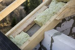Roof construction and insulation with mineral wool. Wooden beams frame on walls of hollow foam insulation blocks. Roofing. Underlayment, water-resistant royalty free stock image
