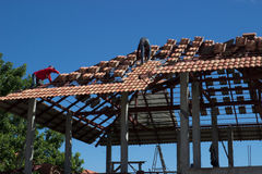 Roof construction. Man worker arrange tile on home roof Stock Photo