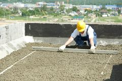 Roof construction. worker roofer leveling with float lute. Manual worker leveling claydite mortar with float lute at roof construction works of residential royalty free stock photography