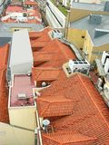 The roof is covered with orange tiles and located on it the system of ventilation and communications and television stock photography