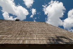 The roof is covered with wooden tiles against the blue sky. The roof is covered with wooden tiles on a blue sky on a clear sunny day. Outdoors Stock Image
