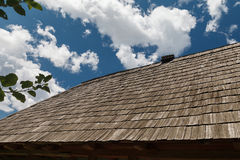 The roof is covered with wooden tiles against the blue sky. The roof is covered with wooden tiles on a blue sky on a clear sunny day. Outdoors Stock Photo
