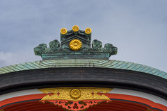 Roof crest at Fushimi Inari Taisha Shinto Shrine. Kyoto, Japan - September 17, 2016: Fushimi Inari Taisha Shinto Shrine. The crest of a roof shines in bronze Stock Images