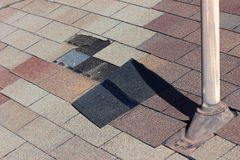 Roof Damage. A close up view of shingles being blown off a roof and other roof damage Royalty Free Stock Image
