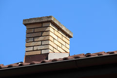 Roof detail of a detached house with red roof tile and beige chi Stock Image