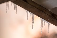 Icicles on a roof with copy space as a wintery background royalty free stock photo