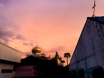 Roof dome in the midst of the sky before dark. Dome of the mosque building amidst a purple and pink sky before nightfall Royalty Free Stock Photo