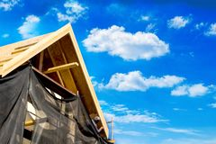 Roof fixing, and a workman. Blue sky & clouds. Long view Stock Images