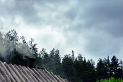 The roof of a forest house with smoke. From a pipe Royalty Free Stock Photo