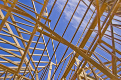 Roof Framing of New Home Construction. Looking at the blue sky through wood roof frame during the construction of a new home Royalty Free Stock Photography
