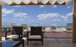 Roof in front of the sea with tanned beds, armchais, blue sky and white clouds Stock Photos