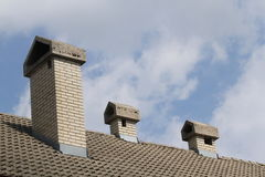 Roof full of chimneys with clouds as background. Three chimneys on the roof with cloudy background Royalty Free Stock Photos